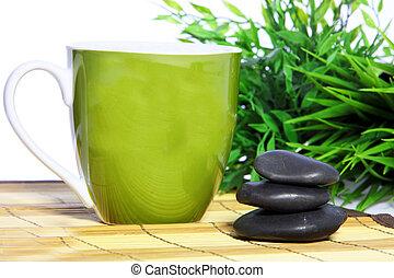 Green mug and spa massage stones