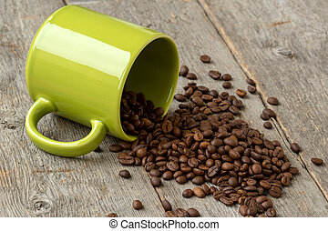 Green mug with scattered coffee beans