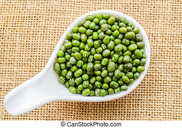 Green mung beans in white spoon.