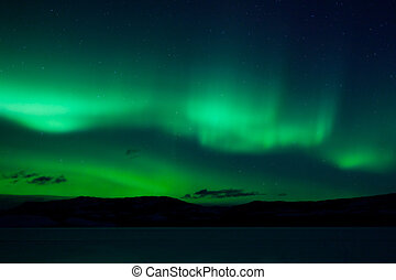 Green northern lights (aurora borealis) substorm above silhouette of hills and clouds.