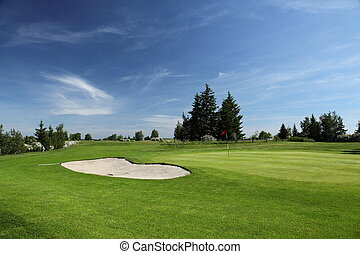green of a beautiful golf course surrounded with bunkers ...