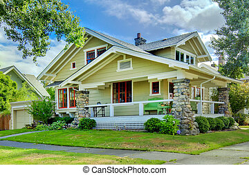 Green old craftsman style home with covered porch.