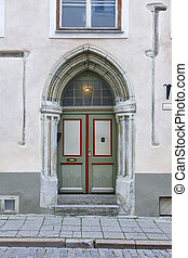 Green old fashioned wooden door on colored facade. Tallinn