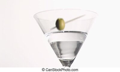 Green olive falling in super slow motion in a gin glass
