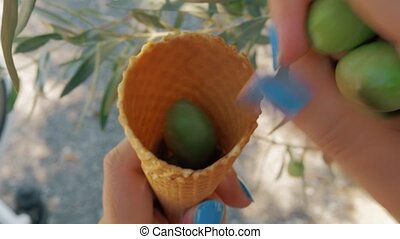 Green olives in waffle cone - Close-up shot of a woman...