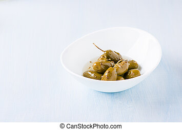 Green olives marinated with coriander in a bowl