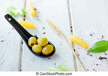 Green olives on black spoon over white wooden background.