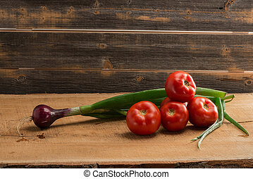 Green onions and tomatoes against the background of old...
