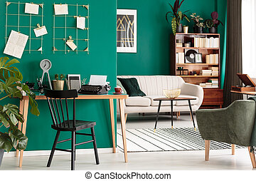 Green open space interior - Black chair at wooden desk in...