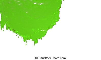 green paint flowing down in slow motion. juice.