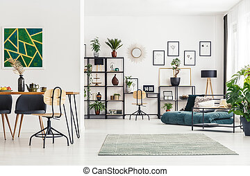Green painting in open space - Wooden chair at table against...