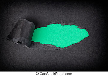 Green paper background appearing behind torn black paper