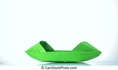 Green paper boat on white background.