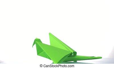 Green paper crane on white background.