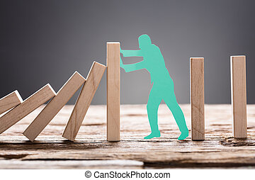 Green Paper Man Stopping Wooden Domino Blocks