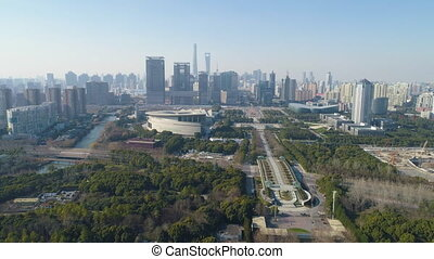 Green Park and Shanghai Downtown at Sunny Day. China. Aerial View. Drone is Flying Forward and Upward. Establishing Shot.