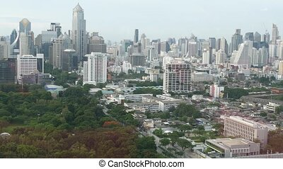 Green park in metropolitan city. Drone view of green trees of Lumphini Park near road and high rise buildings on streets of Bangkok, Thailand.