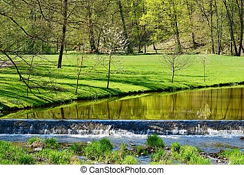 View of a river in the green park in a sunny day. Vlasim castle park.