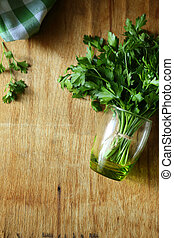 green parsley in a green glass on a wooden table