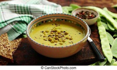 Green pea cream soup in grey bowl - Green vegetables cream...
