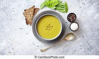 Green pea cream soup in grey bowl placed with spices, fresh...
