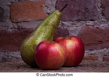 Green pear and red apple on a background wall.