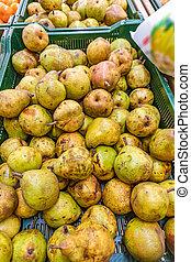 Green pears harvest. Pears in a basket on shelf in supermarket not fresh