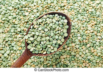green peas in a wooden spoon