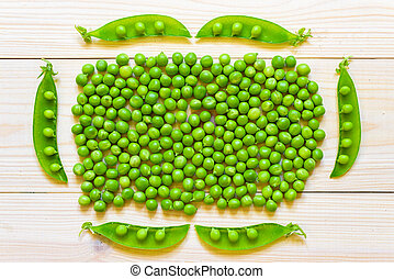 Green peas in white bowl on wooden background, top view or flat