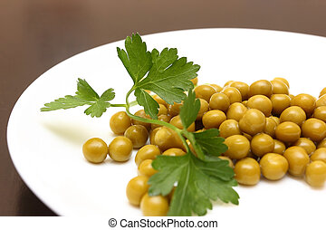Green peas on the plate with parsley. Bokeh effect.