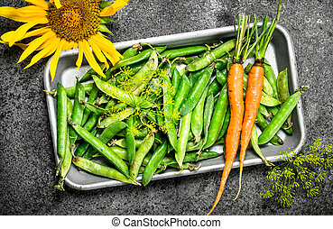 Green peas with carrots on a steel tray.
