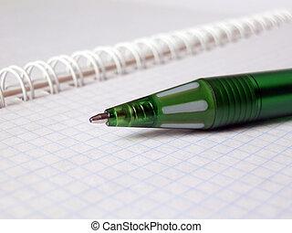 green pen on a notebook