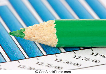 green pencil on financial graphs