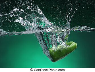 Green pepper falling into water