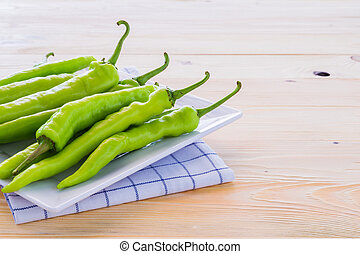 Green peppers on a plate and wooden floors.