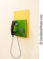 green phone on a beige wall