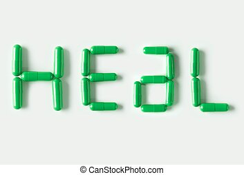 Green Pills capsules in shape of word Heal. Life concept isolated.