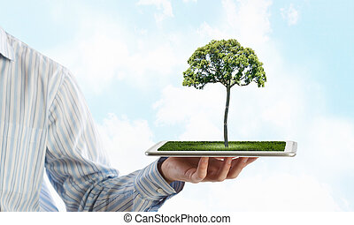 Green planet concept - Human hand holding tablet pc with ...