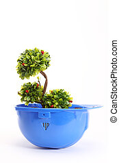 Green plant in blue helmet on white - environmental friendly industry concept