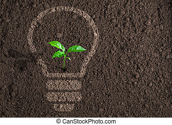 Green plant in light bulb silhouette on soil background