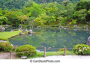 Green plants, mountain, fish, lake with reflection in Japan zen garden