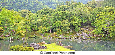 Green plants, trees, mountain, lake with reflection in Japan zen garden