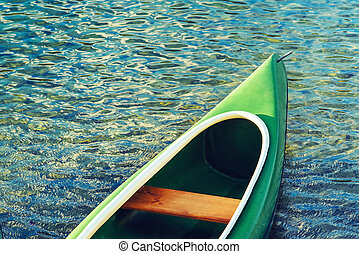 Green plastic canoe on lake