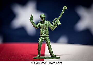 Green plastic soldiers on American flag background