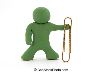 Green plasticine character and big paperclip. Stationery. Isolated over white background