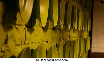 Green plates in a line on the brick wall