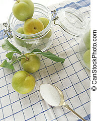 Green plums in jars with sugar