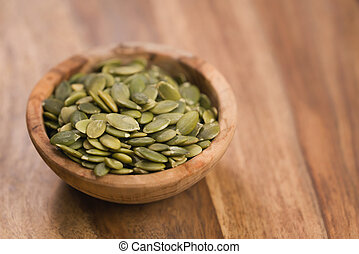 green pumkin seeds in bowl on wooden table