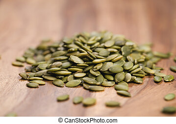green pumkin seeds on wooden table