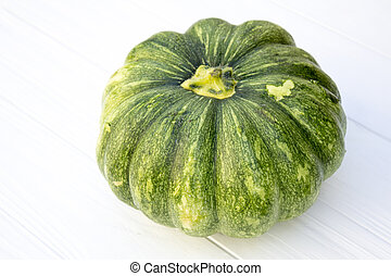 Green pumpkin on a white wooden background